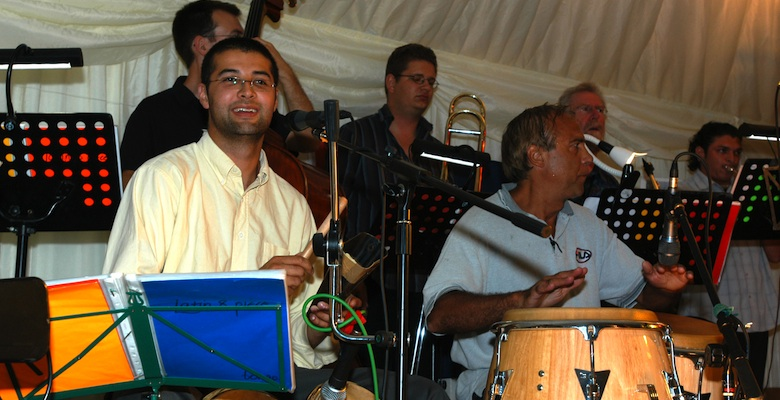 Live Band Jan y su Salsa, bongo player Alejo in the foreground, brass section in the background, at a corporate party in Gloucestershire