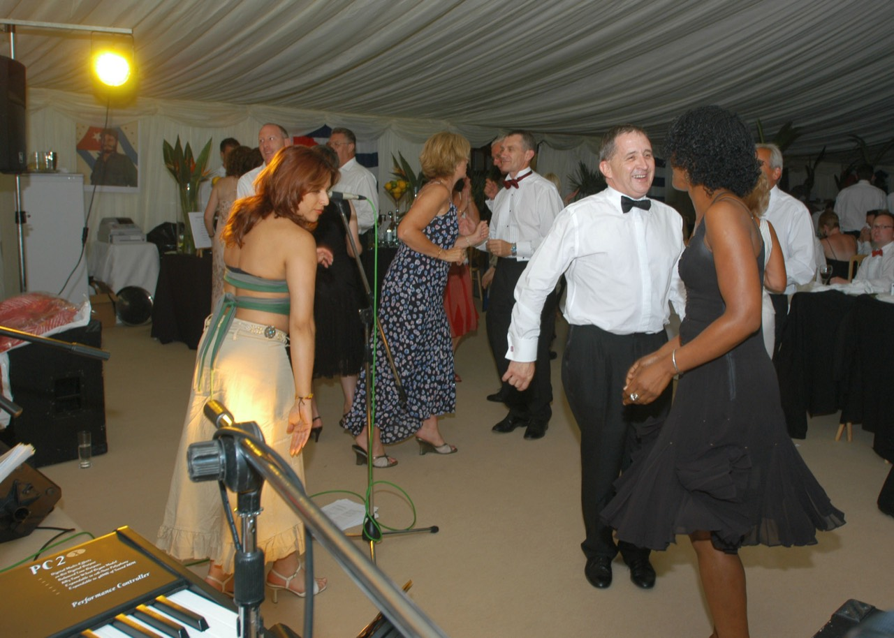 Guests dancing to live latin band Jan y su Salsa at a corporate party in Gloucestershire. Singer Taide in left foreground.