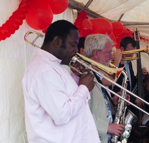 The brass section of latin band Jan y su Salsa, trombonist Harry Brown in the foreground